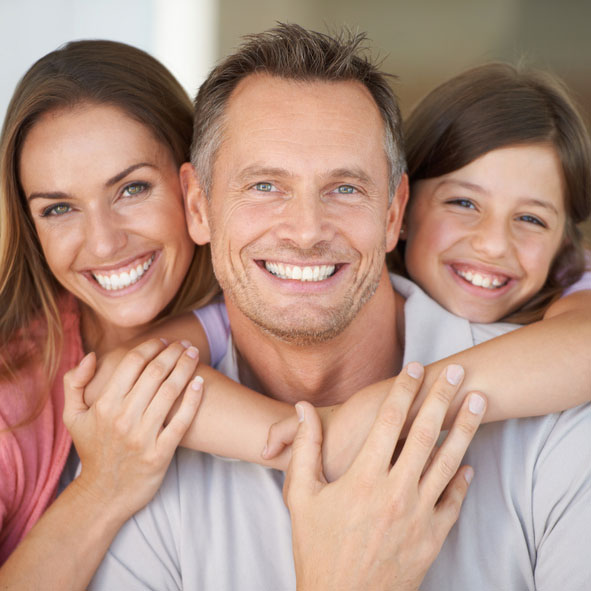A smiling family of patients of Advanced Family Dentistry with healthy teeth